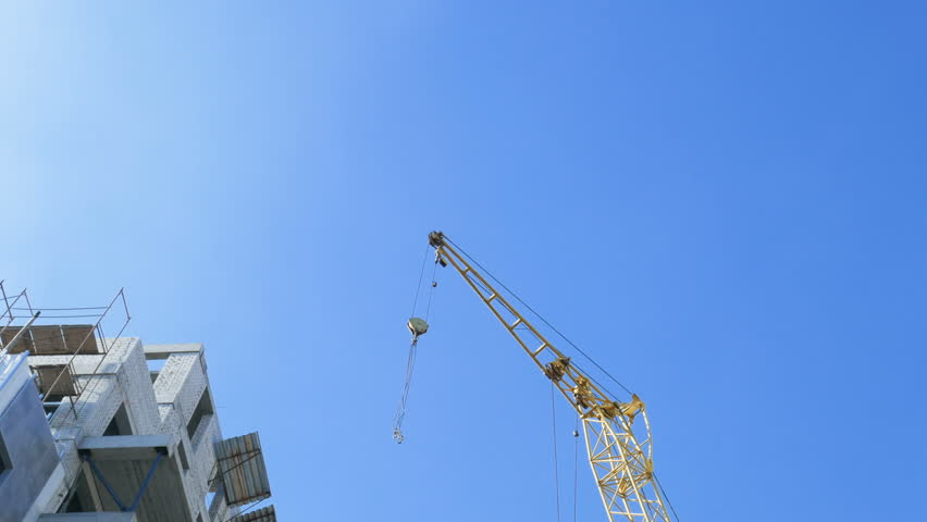 Construction site with cranes, construction of a high-rise building on blue sky background