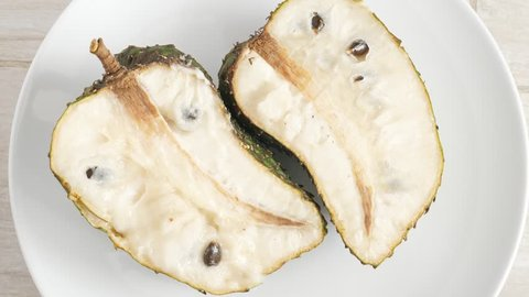 Green soursop graviola, exotic, tropical fruit Guanabana on plate, Rotate