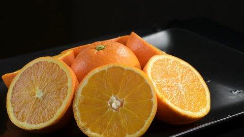Oranges fruit cut in half gyrating on a black tray