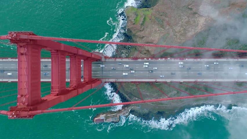 Aerial view of the Golden Gate Bridge. Cloudy fog soaring above the traffic on the red bridge over the green waters of the Pacific Ocean. San Francisco Bay, California, USA. Slow motion 4K drone video | Shutterstock HD Video #1026568967