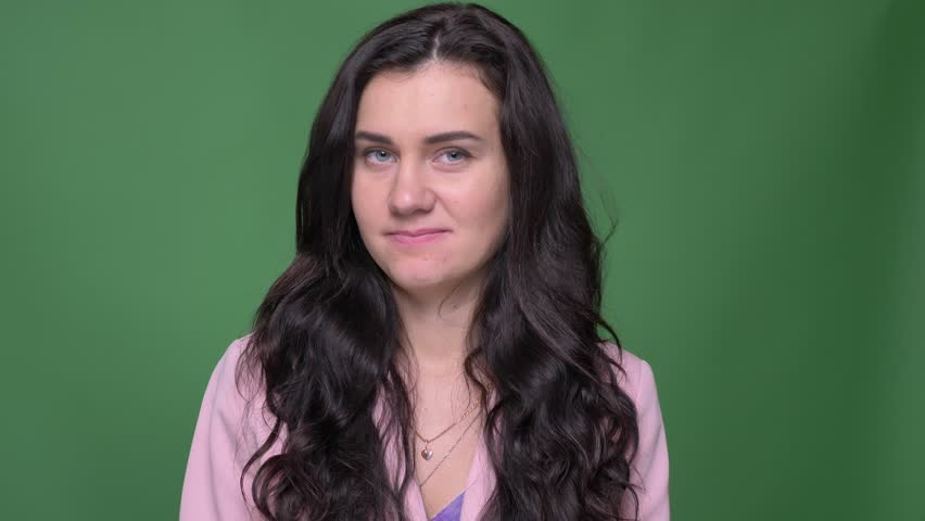 Portrait of serious brunette businesswoman in pink jacket turns head negatively to deny or disagree on green background. | Shutterstock HD Video #1026580157