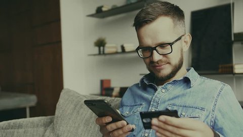 Young european man sitting on the couch, using smart phone for online shopping with credit card on living backround. Indoor.