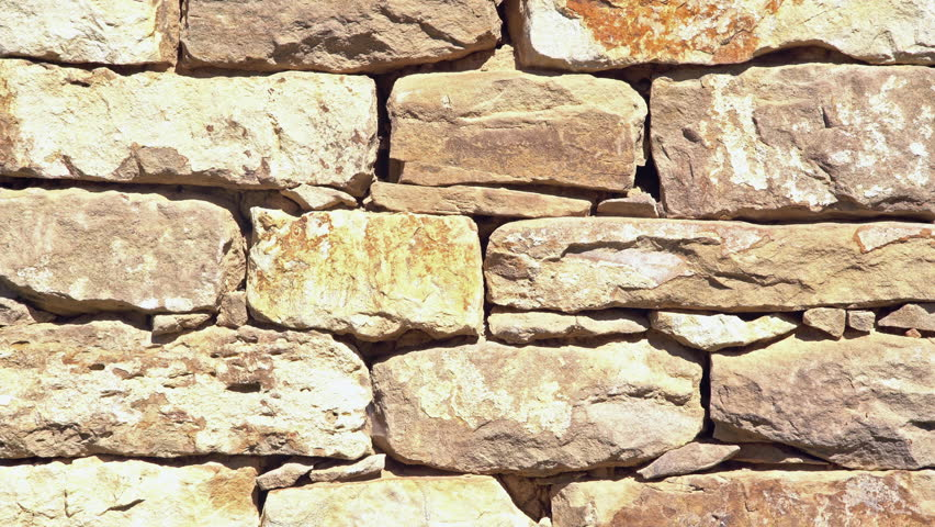 Close up of old flat brown and gray stone wall texture. Layered rocks on a house or building. Architectural stone wall exterior typical in Bulgaria