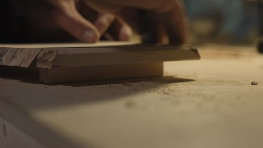 Joiner grinds wood by hand with various tools, sanding machine, grinding tool and sandpaper on the table. Craft factory authentic. | Shutterstock HD Video #1026699797