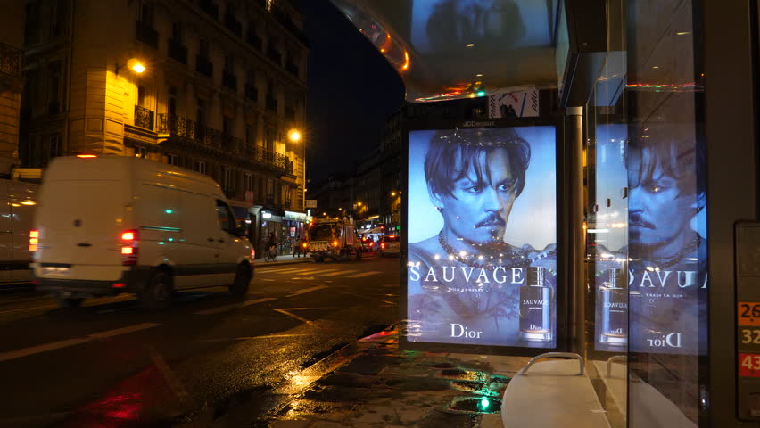 Paris, France - Circa 2019: JCDecaux Modern Electronic advertising board OOH bus station featuring Johnny Depp actor ads for Dior Sauvage Perfume with cars pedestrians and Parisian atmosphere at night
