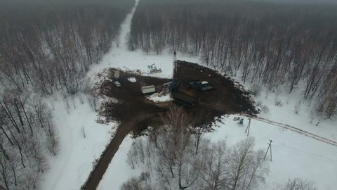 Drilling a deep well with a drilling rig in an oil and gas field in winter forest. The field is located in Kamchatka, Tundra, Yamal, North, West, Siberia, fog, smoke, aerial