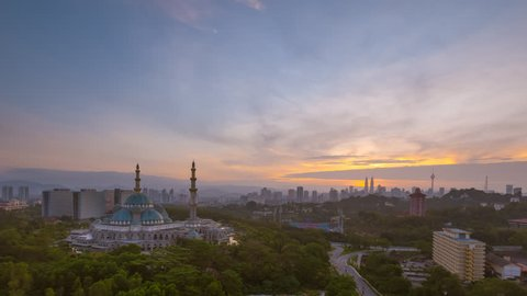 Time lapse. Aerial view of sunrise at Federal Territory Mosque in Kuala Lumpur, Malaysia with silhouette city skyline in dawn.