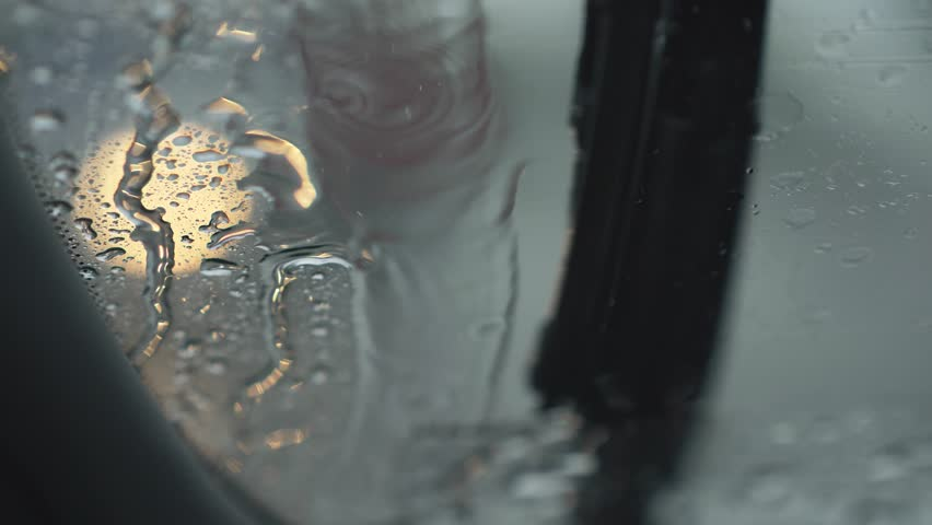 Wipers of a car windshield operating during the rain. Blurred lights of passing-by car traffic is seen throught the windshield. Water is flowing down the windshield. UHD | Shutterstock HD Video #1026763187
