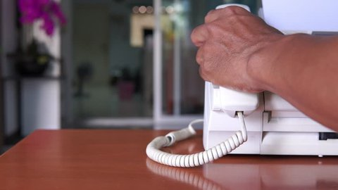 Hand man are using a fax machine in the office Business concept.Fax machine, office equipment
