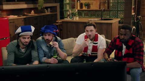Four young friends cheering up for football teams, two of them wear blue football hats, the other two red football scarfs, drinking beer, eating snacks. Football match, true friendship, home party