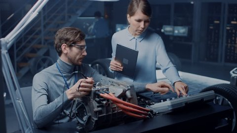 Male and Female Automotive Engineers with a Tablet Computer and Inspection Tools are Having a Conversation While Testing an Electric Engine in a High Tech Laboratory with a Concept Car Chassis.