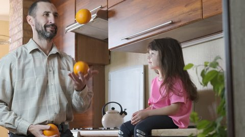 A man juggles in the kitchen. Father with a child juggles with oranges.