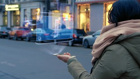 Unrecognizable woman standing on the street interacts HUD hologram with smartphone. Girl in warm clothes with a scarf uses technology of the future mobile screen on background of night city