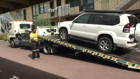 MELBOURNE - APRIL 2019: Truck driver of breakdown support and towing service truck towing a Toyota Land Cruiser Prado vehicle. Every year about 1.2 million cars broken down in Australia.