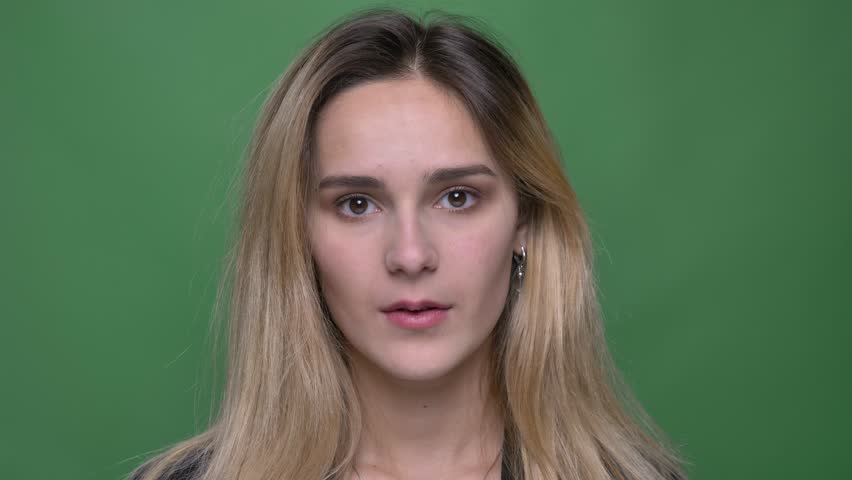 Closeup shoot of young attractive hipster caucasian female being cute and cheerfully smiling while looking straight at camera with background isolated on green | Shutterstock HD Video #1026885317