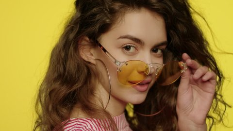Playful woman in yellow glasses looking to camera. Portrait of fashion girl winking eye in studio. Close up of young woman in sunglasses winking to camera on yellow background. Fashion model wink eye