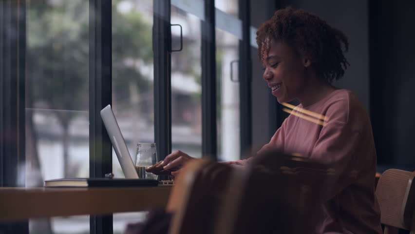 Side view of pretty young African woman typing on laptop chatting online big smile on face. Slow motion of happy Black young woman surfing the internet using computer laughing indoor by the window | Shutterstock HD Video #1026906947