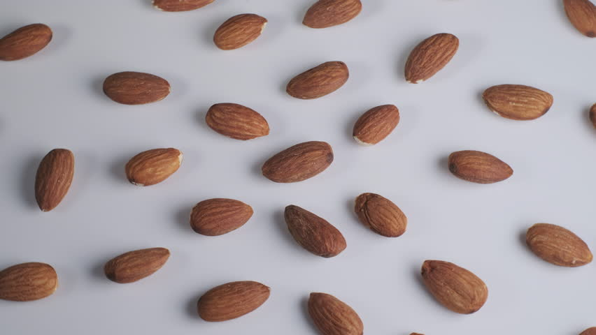 Whole almond on white background. Rotating motion. Cinematic graded footage.