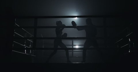Coach training female boxer on the boxing ring. Silhouette. Boxing concept