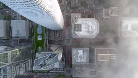 SAN FRANCISCO, CA, USA. Slow motion aerial 4K view of the unique architecture and distinguishable rooftops in San Francisco downtown. Obelisk-shaped skyscrapers covered with thick fog.