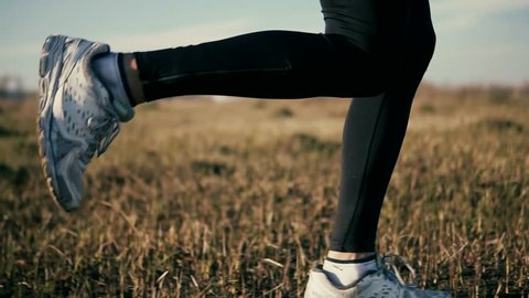 Man Running Slow Motion.Close Up Shot Of A Male Run In Countryside Field.Runner Close Up Of Legs.Close Up Legs Running Slow Motion On Trail. Foot And Shoes Man Athlete Legs Close-Up Jogging.