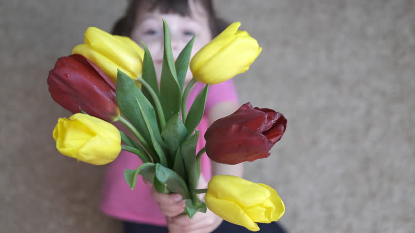 The child gives flowers. Mothers Day.