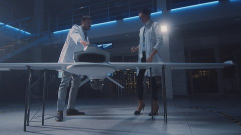Meeting of Aerospace Engineers Working On Unmanned Aerial Vehicle / Drone Prototype. Aviation Scientists in White Coats Talking. Commercial Aerial Surveillance Aircraft in Industrial Laboratory