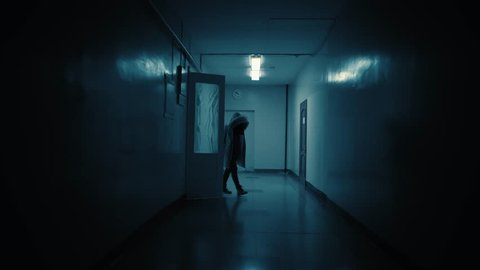 Tracking inside a long dark gloomy corridor. A dark silhouette of a girl dressed in a parka stops in front of the camera.White big clocks hang on the wall and show ten to eleven.Concept of horror.