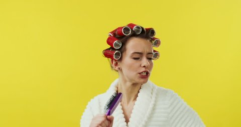 Portrait shot of the young joyful and charming woman in the white bathing robe and curlers on the head posing funny to the camera while singing in the comb like in the microphone on the yellow