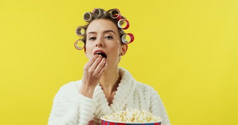 Portrait shot of the funny Caucasian young woman with curlers and in bathrobe coming in front of the camera with popcorn, eating it and going away on the yellow wall background.