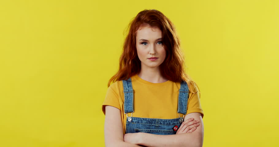 Portrait of the beautiful red haired Caucasian young girl standing in front of the camera on the yellow wall and doing a gesture with her finger to mouth like be silent, hush. | Shutterstock HD Video #1027042067