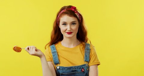 Portrait of the charming young stylish girl smiling to the camera and biting a big lollipop on the yellow wall background.