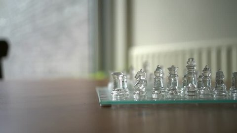 A game of transparent, glass chess and its pawns, sitting on a wood table inside a home. The camera slowly spins around the thinking game. A big window and chair are blurry in the background.
