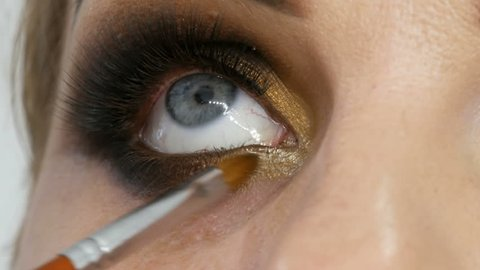 Master make-up artist apply professional make-up golden smoky eyes in a beauty salon to a fat woman model with blue eyes close up