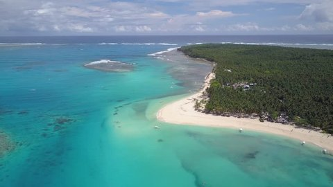 Aerial tracking shot pan right of wonderful island with palm trees and clear blue waters in Siargao, the Philippines