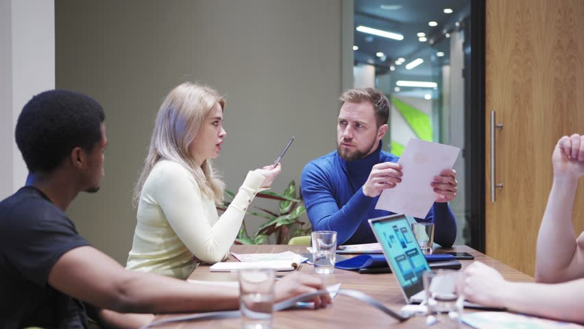 Tracking shot of young business team sitting at table and having meeting. Manager asking employees to explain negative financial report | Shutterstock HD Video #1027164887