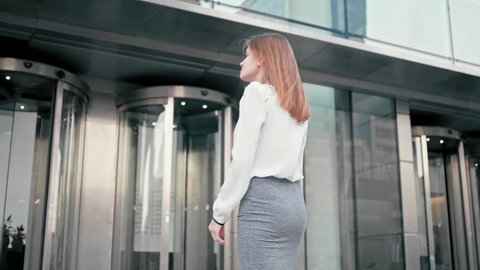 Anonymous Slender Caucasian Business Woman Manager in White Shirt is Entering into Office Building via Glass Revolving Door. Back View Low Angle 4K Slow Motion Corporate Shot