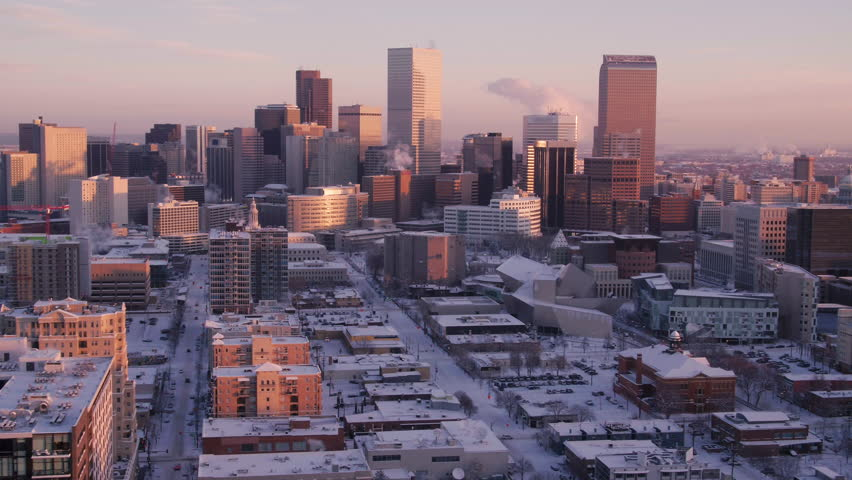 Frosted snowy sunrise pan above Denver, Colorado, construction crane in foreground, iconic skyline in background, telephoto aerial | Shutterstock HD Video #1027225457