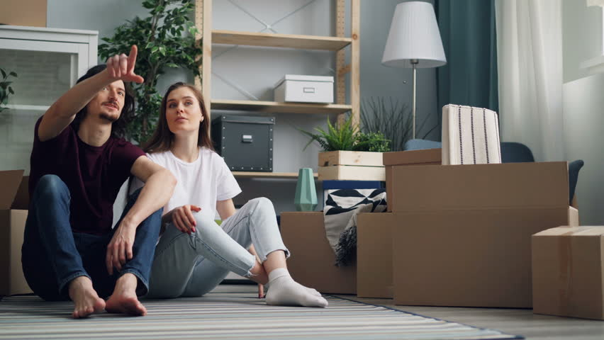 Young beautiful couple is talking and kissing sitting on floor with boxes moving in new flat. Happy people are discussing relocation and dreaming about future. | Shutterstock HD Video #1027227137