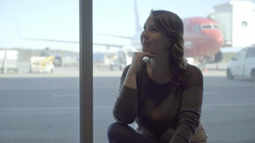 Young tourist woman in the airport terminal, looking through the window at plane   Shutterstock HD Video #1027227527