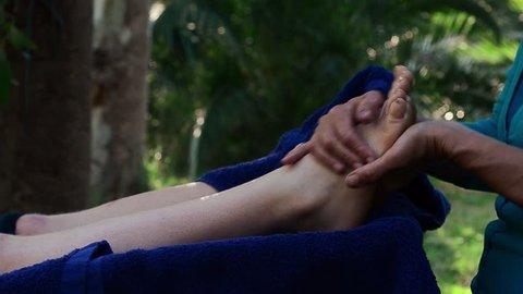 Reflexology foot massage in peaceful zen garden, female massage therapist preforming reflexology treatment at a health spa, young woman enjoying a pampering massage at a retreat holiday