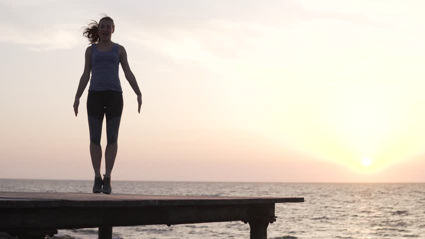 Woman doing Jumping Jacks by the sea. Fit healthy sport girl on rocks beach. Yoga warm up routine in Cyprus. Training overlooking a beautiful sunset   Shutterstock HD Video #1027307477