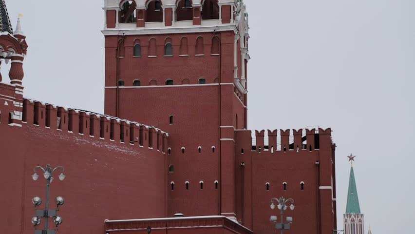 MOSCOW, RUSSIA - DECEMBER, 2018: Gimbal slow motion tilt up shot of Spasskaya clock tower and Moscow Kremlin red brick wall on cloudy winter sky background with russian flag waving