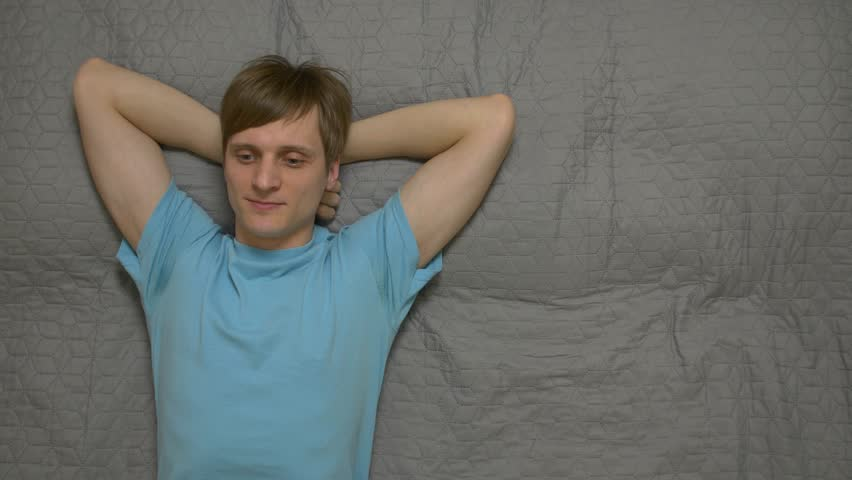 Young man dreams on bed resting daytime sleep thinks positive smile male 30 years old in blue t shirt caucasian white european lying on the bed gray sheet top view. | Shutterstock HD Video #1027347257