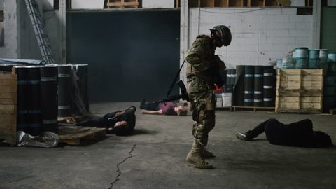 A special ops military SWAT team member emerges from dark smoke filled warehouse walking towards camera taking out bad guys in warehouse under daytime lighting. Daytime wide shot on RED camera