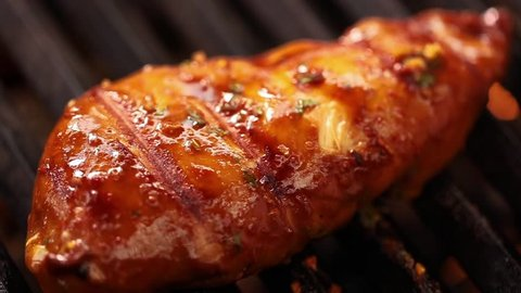 Closeup shot of cooking grilled chicken in barbecue griller. Barbecuing chicken for party.Preparing Delicious Grilled chicken.Grilled chicken piece on barbecue.Cinematic shot of barbecuing Meat Loaf.