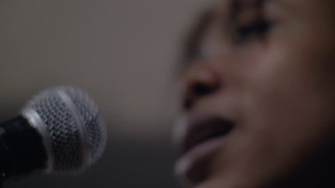 Facing a silvery and black microphone, a black African American woman young with brown skin, thick lips sings song affectionately under the bright light black singer singing in studio with emotion