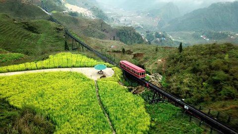 Aerial forward descent Mountain red train railway. Majestic panorama rice fields mountain canyon view of Valley Vietnam