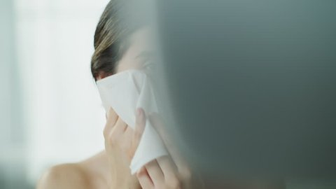 Close up of woman washing face with washcloth in mirror / Cedar Hills, Utah, United States