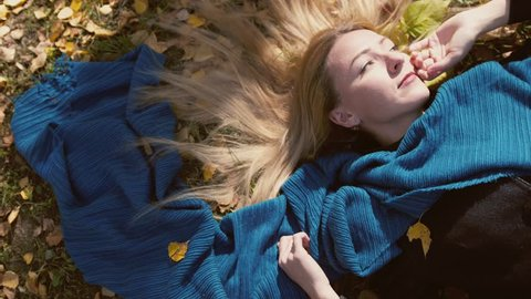 Top view of autumn blond beautiful woman lying over leaves on sunny day. slow motion. 3840x2160